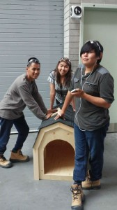 Bradley Blackduck (far right) shows off the doghouse he built in construction class with his classmates.