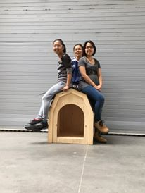 Saveah (middle) with fellow participants Napassi (left) and Sandra (right) show off the doghouse they built in construction class.